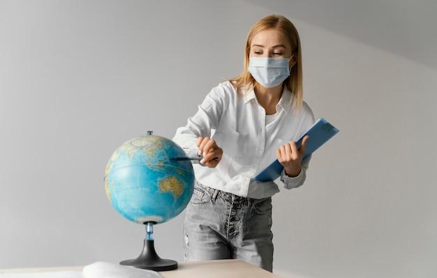 Vista frontal de la profesora en el aula con portapapeles apuntando al mundo