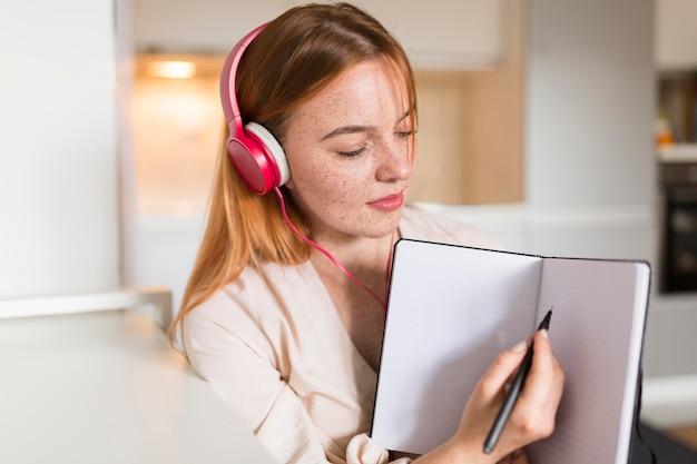 Vista frontal de la profesora con auriculares apuntando a la agenda de la clase en línea