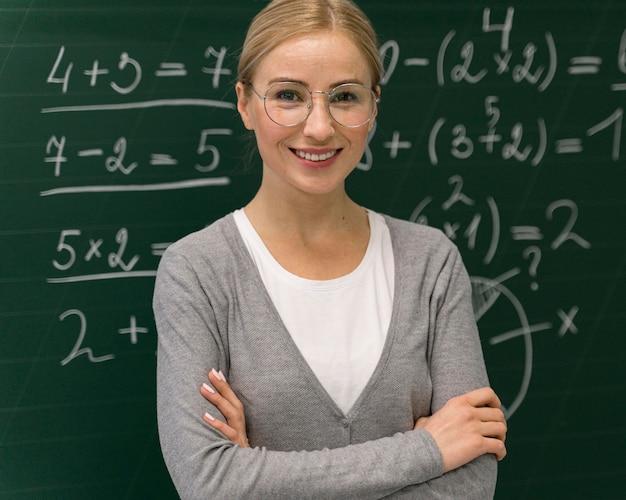 Vista frontal de la profesora sonriente posando delante de la pizarra
