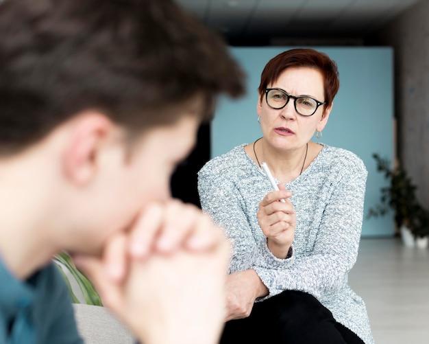 Vista frontal del psicólogo dando consejos al paciente.