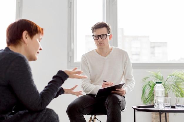 Vista frontal del psicólogo que consulta a un paciente