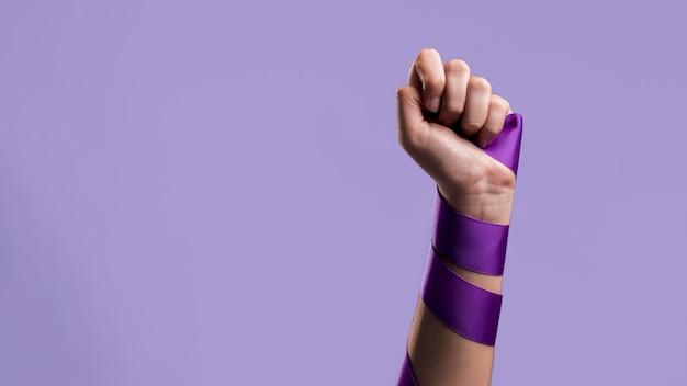 Vista frontal del puño de una mujer con cinta y espacio de copia