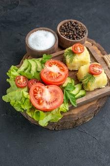 Vista frontal del queso de verduras frescas picadas y enteras en la tabla de cortar y especias sobre superficie negra