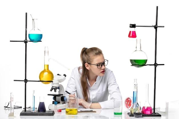 Vista frontal químico femenino en traje médico escribiendo notas sobre fondo blanco química salud pandémica covid