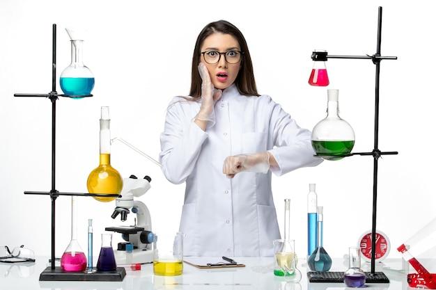 Vista frontal químico femenino en traje médico estéril comprobando el tiempo sobre fondo blanco virus covid- ciencia pandémica
