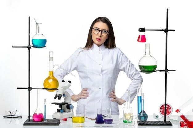 Vista frontal químico femenino en traje médico estéril de pie sobre fondo blanco enfermedad viral covid-ciencia pandémica