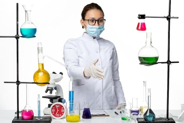 Vista frontal químico femenino en traje médico máscara saludando a alguien sobre fondo blanco laboratorio de química de virus covid- splash