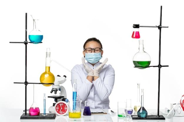 Vista frontal químico femenino en traje médico con máscara sentado frente a la mesa con soluciones sobre fondo blanco laboratorio de química de virus covid splash