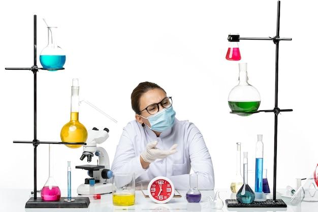 Vista frontal químico femenino en traje médico con máscara sentado con soluciones sobre fondo blanco laboratorio de salpicaduras de química de virus covid