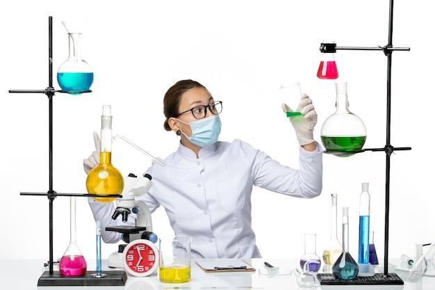 Vista frontal químico femenino en traje médico con máscara sosteniendo una solución verde sobre fondo blanco claro, laboratorio de salpicaduras de química de virus covid-