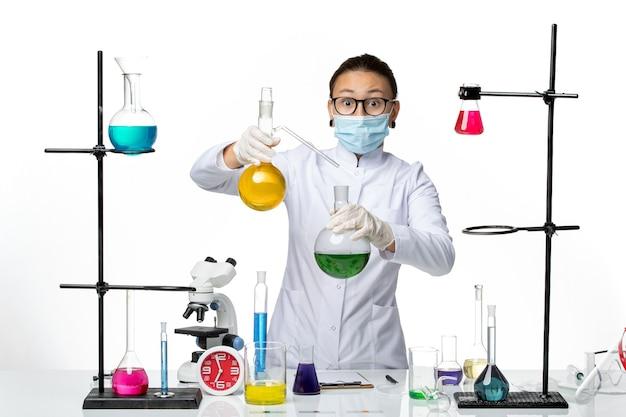 Vista frontal químico femenino en traje médico con máscara trabajando con soluciones sobre fondo blanco laboratorio de química de virus covid splash