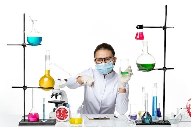 Vista frontal químico femenino en traje médico con solución de sujeción de máscara sobre el fondo blanco claro, laboratorio de salpicaduras de química de virus covid-