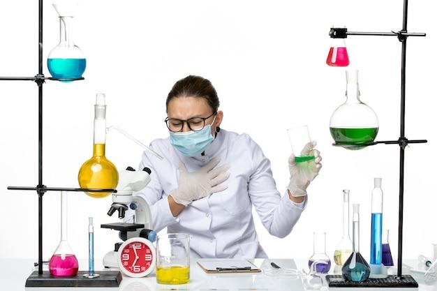 Vista frontal químico femenino en traje médico con solución de sujeción de máscara sobre fondo blanco química de virus de laboratorio de salpicaduras covid