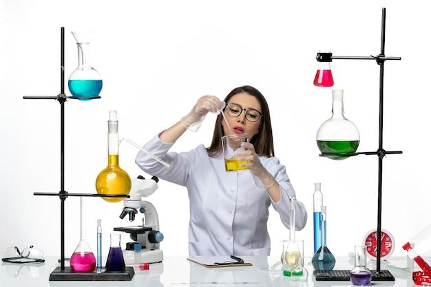 Vista frontal químico femenino en traje médico trabajando con soluciones sobre fondo blanco virus de laboratorio covid-ciencia pandémica