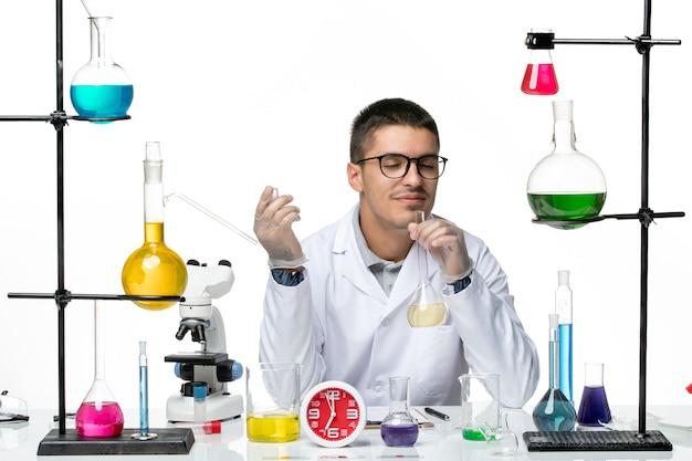 Vista frontal químico masculino en traje médico blanco con matraz con solución sobre fondo blanco laboratorio de covid-pandemia de ciencia de virus