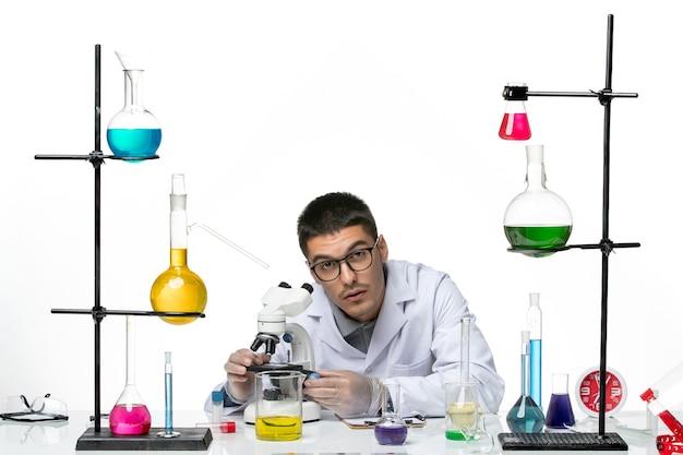 Vista frontal químico masculino en traje médico blanco con microscopio sobre fondo blanco claro laboratorio de virus covid - ciencia de la enfermedad