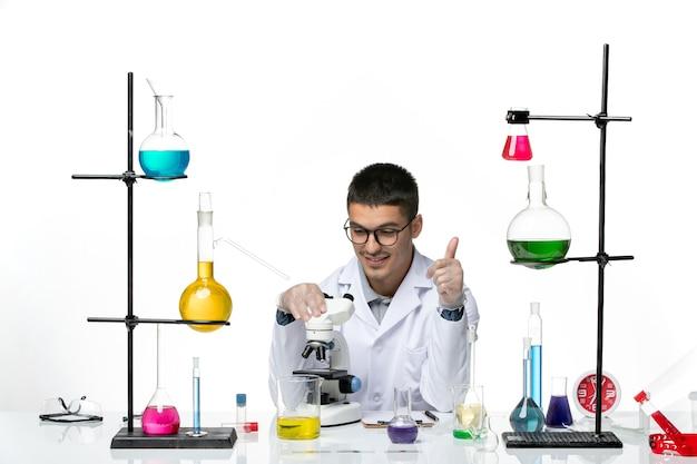 Vista frontal químico masculino en traje médico blanco con microscopio sobre fondo blanco claro virus covid - ciencia de laboratorio de la enfermedad