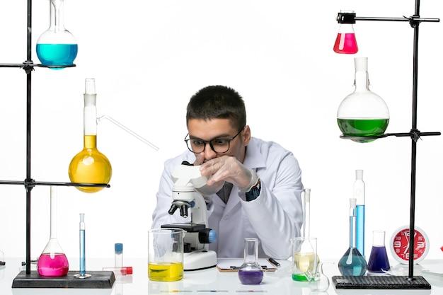 Vista frontal químico masculino en traje médico blanco con microscopio sobre fondo blanco laboratorio de virus covid- ciencia de la enfermedad