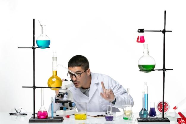 Vista frontal químico masculino en traje médico blanco con microscopio sobre fondo blanco virus covid- ciencia de la enfermedad