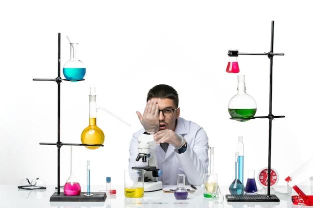 Vista frontal químico masculino en traje médico blanco con microscopio en el suelo blanco virus covid- ciencia de laboratorio de la enfermedad