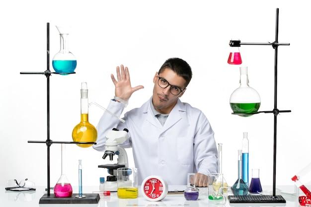 Vista frontal químico masculino en traje médico blanco saludando a alguien sobre fondo blanco laboratorio de covid-pandemia de ciencia de virus