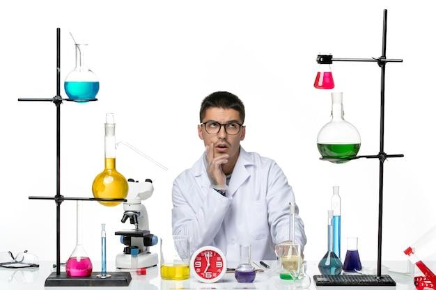 Vista frontal químico masculino en traje médico blanco sentado y pensando en el laboratorio de ciencia de la enfermedad del virus de fondo blanco covid