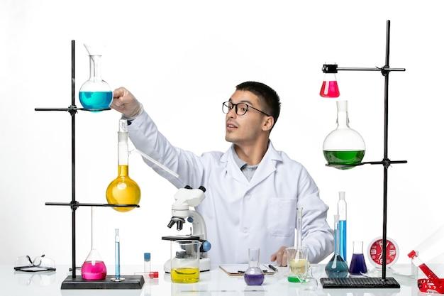 Vista frontal químico masculino en traje médico blanco sentado con soluciones sobre fondo blanco claro laboratorio de virus ciencia de la enfermedad covid