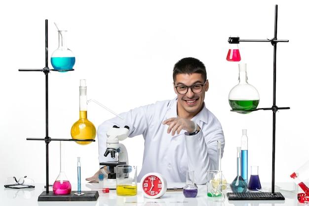 Vista frontal químico masculino en traje médico blanco sentado con soluciones sobre fondo blanco pandemia de covid de ciencia de virus de laboratorio
