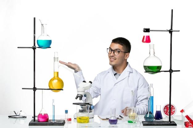 Vista frontal químico masculino en traje médico blanco sentado con soluciones y sonriendo sobre fondo blanco laboratorio de virus ciencia de la enfermedad covid