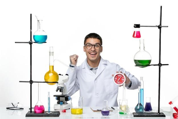 Vista frontal químico masculino en traje médico blanco sosteniendo relojes rojos sobre fondo blanco laboratorio de ciencias de la enfermedad del virus covid