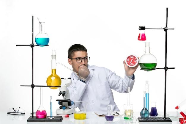 Vista frontal químico masculino en traje médico blanco sosteniendo relojes sobre fondo blanco claro laboratorio de ciencias de la enfermedad del virus covid