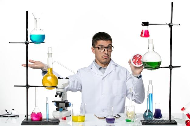 Vista frontal químico masculino en traje médico blanco sosteniendo relojes sobre fondo blanco laboratorio de ciencias de la enfermedad del virus covid