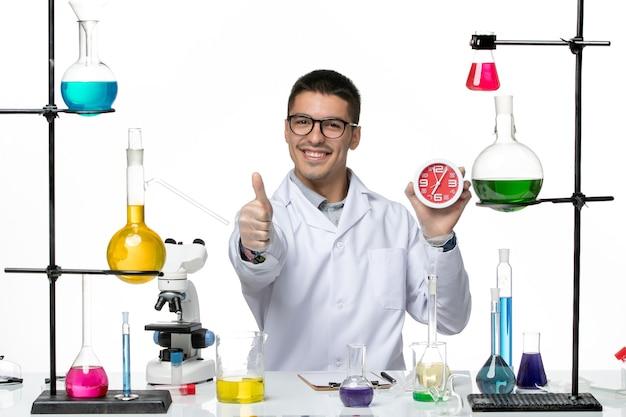 Vista frontal químico masculino en traje médico blanco sosteniendo relojes sonriendo sobre fondo blanco laboratorio de ciencias de la enfermedad del virus covid
