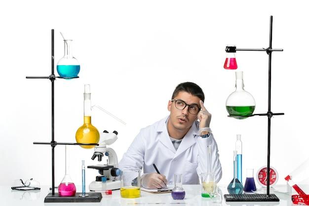 Vista frontal químico masculino en traje médico sentado y escribiendo algo sobre fondo blanco ciencia de la enfermedad de salpicaduras de virus covid