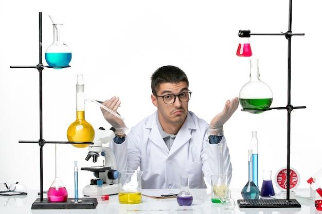 Vista frontal químico masculino en traje médico sentado con soluciones sobre fondo blanco ciencia de la enfermedad de salpicaduras de virus covid