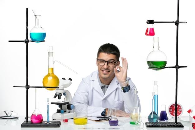 Vista frontal químico masculino en traje médico sentado y sonriendo sobre fondo blanco claro virus covid splash enfermedad ciencia