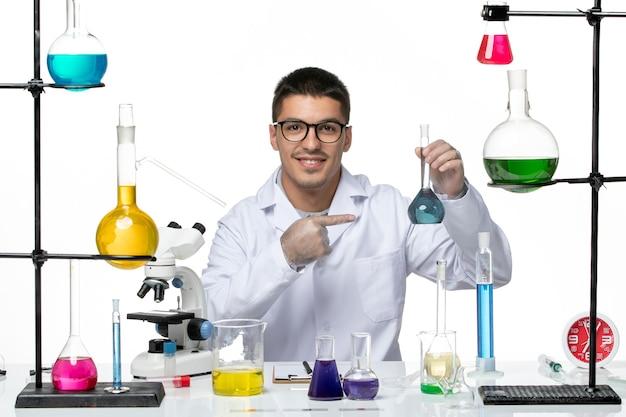 Vista frontal químico masculino en traje médico sentado sosteniendo la solución sobre fondo blanco virus covid- ciencia de la enfermedad de salpicaduras