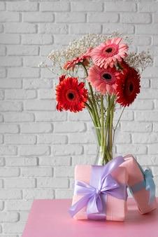 Vista frontal del ramo de flores en un jarrón con cajas de regalo
