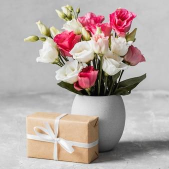 Vista frontal ramo de rosas en un jarrón junto a un regalo envuelto
