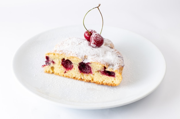 Vista frontal de la rebanada de pastel de cereza dentro de la placa con azúcar en polvo en la superficie blanca de la galleta de pastel de masa de azúcar dulce hornear