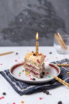 Vista frontal de la rebanada de pastel dentro de la placa con velas encendidas