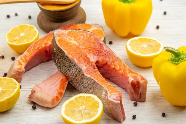 Vista frontal de las rebanadas de carne fresca con rodajas de limón sobre el fondo blanco animal pescado costilla foto plato comida comida