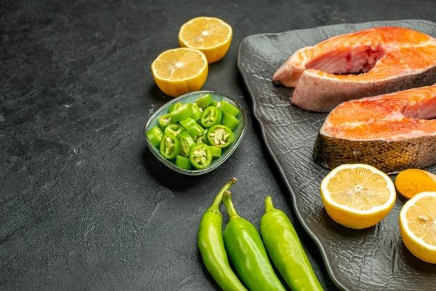 Vista frontal rebanadas de carne frita con pimientos y limón sobre el fondo oscuro color comida plato costilla ensalada madura comida