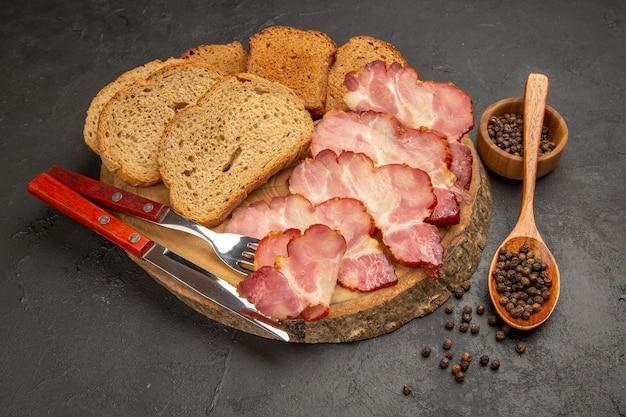 Vista frontal de las rebanadas de jamón fresco con bollos y rebanadas de pan en un bocadillo oscuro color carne comida comida