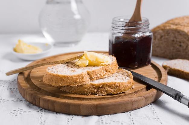 Vista frontal de rebanadas de pan con mermelada y mantequilla