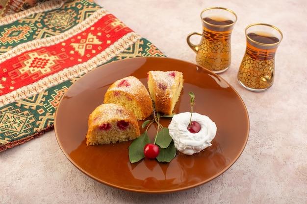 Una vista frontal de las rebanadas de pastel de cereza con crema en el escritorio rosa
