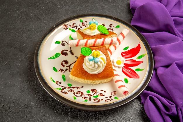 Vista frontal de las rebanadas de pastel cremoso en el escritorio de color gris oscuro pastel de té pastel de galletas masa dulce