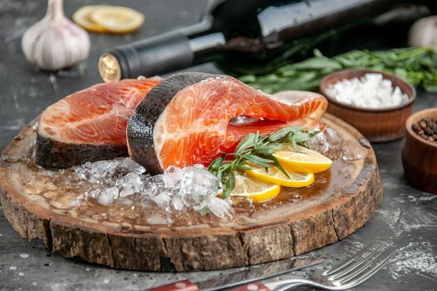 Vista frontal de las rebanadas de pescado crudo con rodajas de limón y hielo en el color de la comida del plato de mariscos de la comida de barbacoa gris