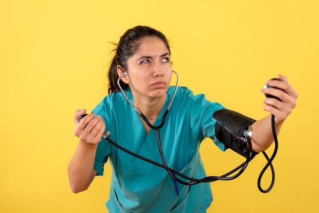 Vista frontal reflexiva joven doctora con esfigmomanómetro sobre fondo amarillo