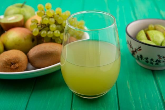Vista frontal de un refresco en un vaso con manzanas verdes uvas verdes kiwi y pera en un plato sobre un fondo verde